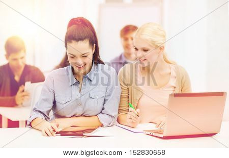education, technology and internet concept - two smiling students with laptop computer, tablet pc and notebooks at school