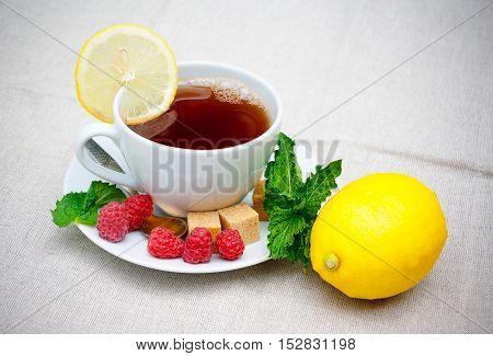Tea with mint brown sugar raspberry and lemon on table
