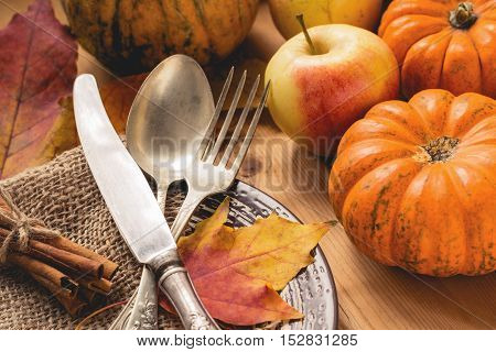 Autumn table setting for Thanksgiving dinner with pumpkins, apples, cinnamon sticks, fallen leaves and tableware on a plate.