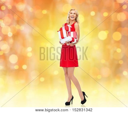 people, christmas, birthday and holidays concept - happy young woman in red dress holding gift boxes over lights background