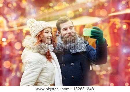 holidays, winter, christmas, technology and people concept - happy couple of tourists in warm clothes taking selfie with smartphone in old town