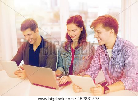 education, technology, school and internet concept - three smiling students with laptop and tablet pc at school