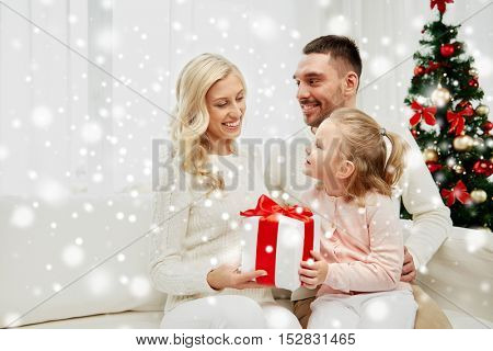 family, christmas, holidays and people concept - happy mother, father and little daughter with gift box sitting on sofa at home