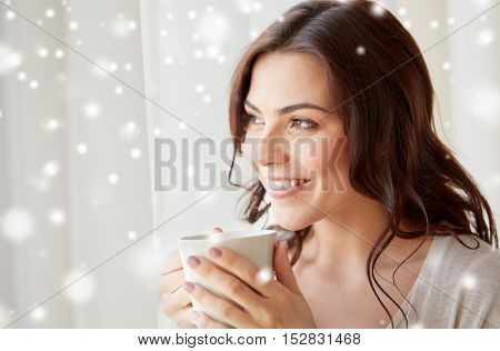 people, drinks, winter, christmas and leisure concept - close up of happy young woman with cup of tea or coffee at home over snow