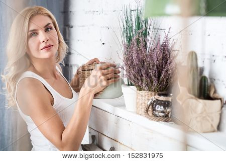 Everything in place. Beautiful blond woman standing near decorated shelf and ordering it.