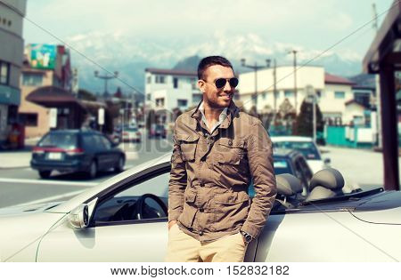 travel, tourism, transport, leisure and people concept - happy man near cabriolet car over city in japan background