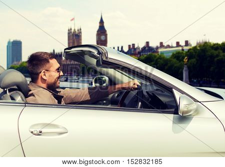 travel, tourism, transport, leisure and people concept - happy man near cabriolet car over london city background