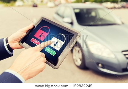 transport, safety, security, technology and people concept - close up of male hands with lock and unlock icon on tablet pc computer screen and car outdoors