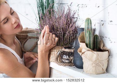 Flower power. Pretty looking blond woman touching decorative flower.