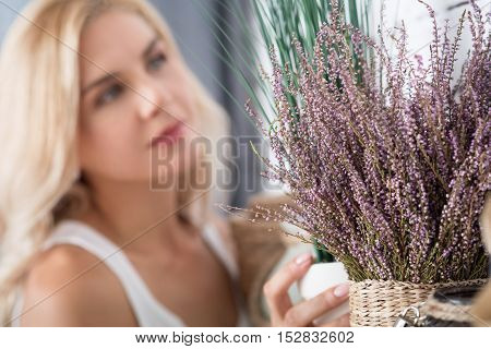 Perfect match. Close up view of fake dry decorative flower on background of pretty blurred blond woman.