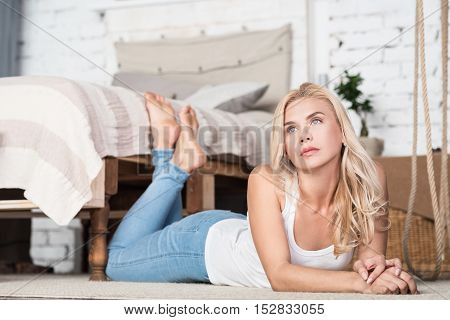 Deep thought. Thoughtful blond woman lying on floor in good decorated bedroom.