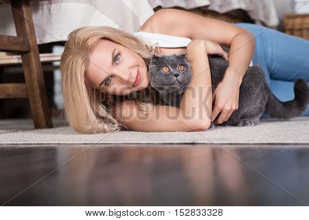 Got you. Happy blond lady lying on carpet in bedroom and hugging grey kitten.