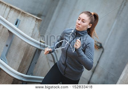 Young female running up the stairs with earphones