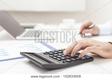 Side View Of Man's Hands Using Calculator