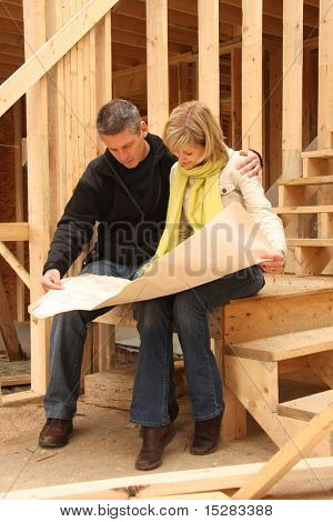 Happy couple going over the blue prints of their new home still under construction.