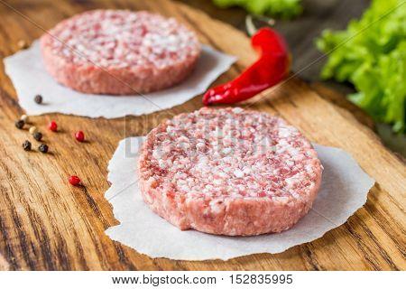 Raw fresh burger meat patties on wooden chopping board