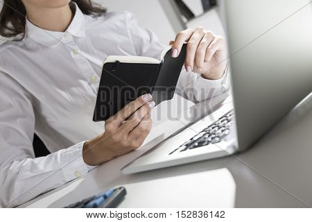 Close up of elegant woman's hands holding a tiny black notebook. Concept of journalist's work and blogger's life