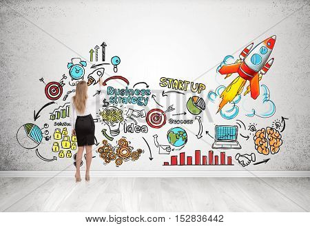 Rear view of woman drawing and standing near concrete wall with colorful business sketches on it. Concept of making your dreams come true. 3d rendering.
