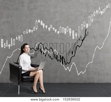 Smiling young woman in leather armchair is sitting near concrete wall with graphs. Concept of statistics in business