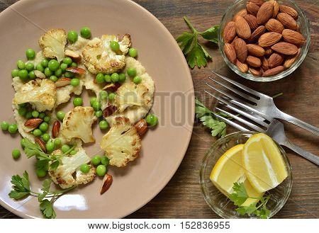 Salad with roasted cauliflower and green peas almonds served on vegetable puree, top view