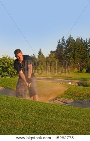 Golfer chipping out of the sand