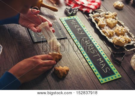 Woman decorating gingerbread cookies on woodem background