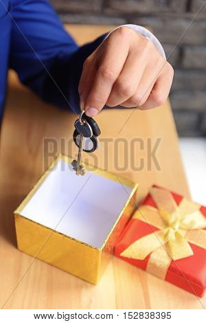 man holding keys from a new house in front of a gift box