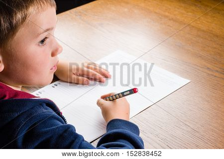 Looking over the shoulder of a boy doing homework in a living room.