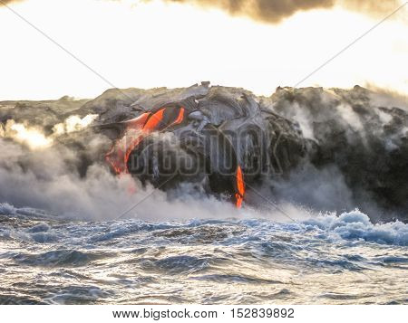 Volcanic activity with smoke and steam given off by lava contact with Pacific Ocean. Kilauea Volcano in Hawaii Volcanoes National Park, Big Island, United States. Sea view of lava rivers into the sea.