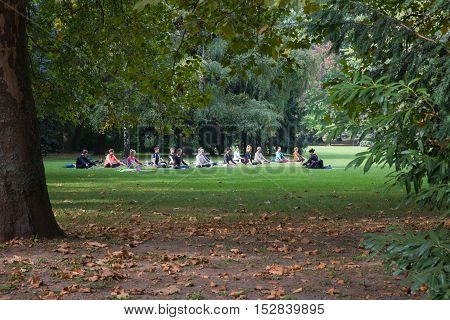 Budapest, Hungary - October 2 2016. Park Margit. Yoga in the park Margaret, Budapest, Hungary. A group of young people under the guidance of an Asian woman doing yoga.