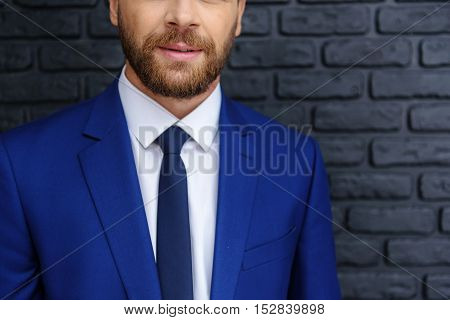 close up of a successful businessman in expensive blue suit indoors