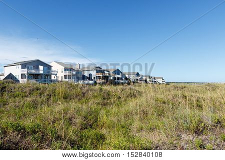 Wide angle view of luxury beach vacation rental homes on the green grass covered sand dunes; Sunset Beach, North Carolina