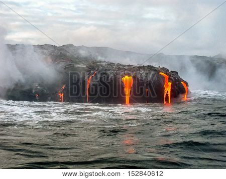 Scenic sea view from the boat of Kilauea Volcano in Hawaii Volcanoes National Park, while erupting lava into Pacific Ocean, Big Island, Hawaii.
