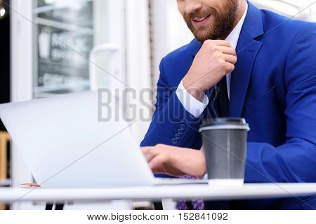 happy elegant man in blue costume sitting with coffee at the table outdoors, selective focus