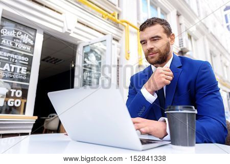 bearded man working on laptop and drinking tea outdoors