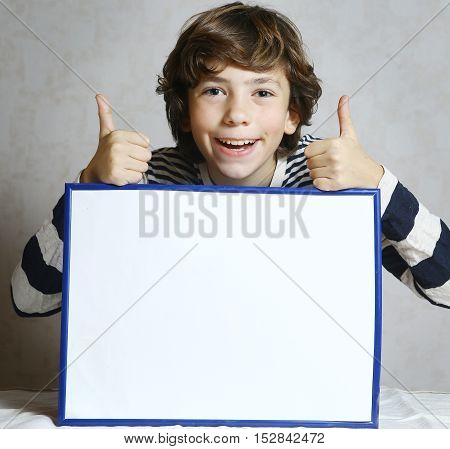 preteen handsome boy with thumbs up hold blank white rectangle paper sheet in frame. Boy copy space. Smiling boy.
