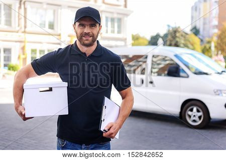ready to deliver, young postman walking to the house with a tablet and box