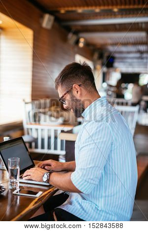 Handsome casual man working on a computer in a cafe.