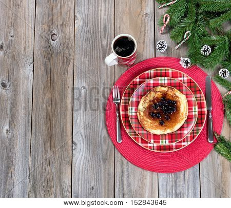 Overhead view of a festive Christmas breakfast meal and coffee with evergreen branches on top of rustic wood.
