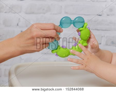 Mother's and baby's hands with new toy