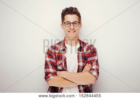 Portrait of confident young man in shirt crossing his arms