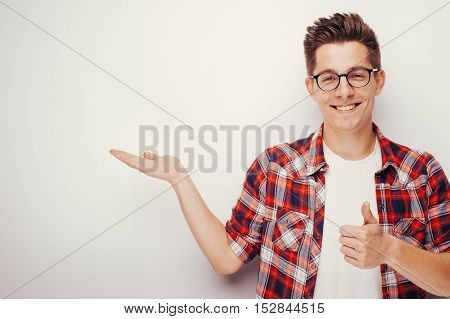 Happy man in glasses and red shirt showing thumb up. Presentation of goods