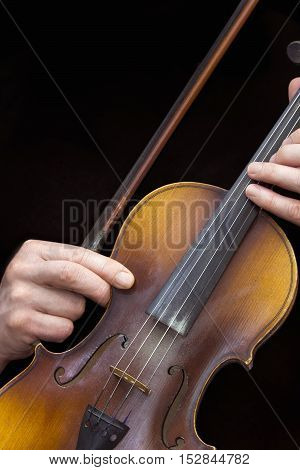 Close view of men's hands with old violin in a black background