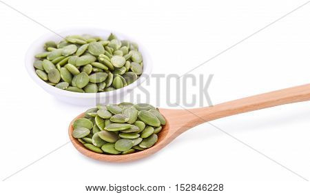 pumpkin seeds in wooden spoon and white bowl isolated on white