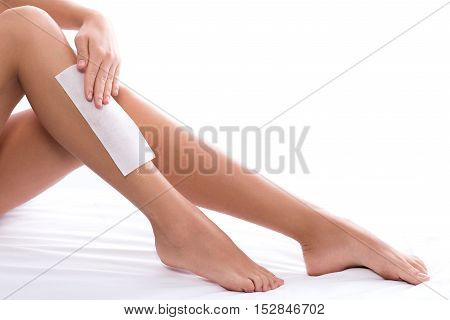 Close up of young woman applying depilation strip paper on her leg carefully. Isolated