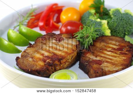 grilled two pork chop with vegetable on white plate