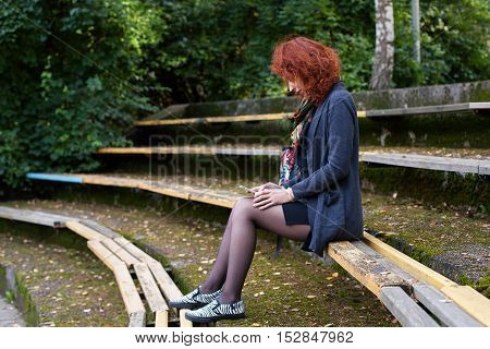Ginger woman sitting on the bench in the autumn park and looking at the screen of a smartphone