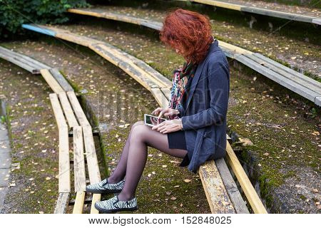 Girl sitting on a park bench and flipping a tablet