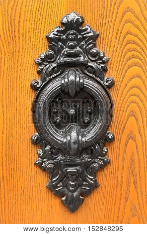 Old door knocker closeup on wooden background