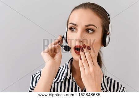 Surprised female operator is wearing headphones and microphone. She is standing and covering her open mouth by hand. Isolated